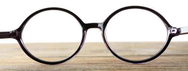 Eye glasses on wooden table on white background