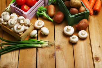 Different vegetables in boxes on wooden background top view
