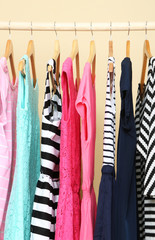 Colorful clothes on hangers in room