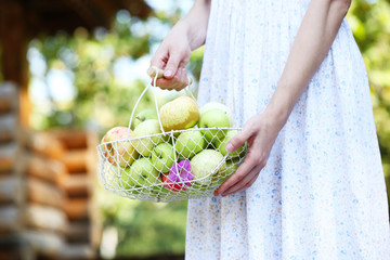 Girl holding basket of apples outdoors