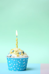 Delicious birthday cupcake on table on light green background