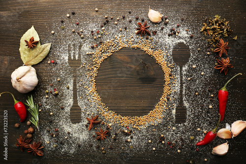 Spices on table with cutlery silhouette, close-up - 73223520