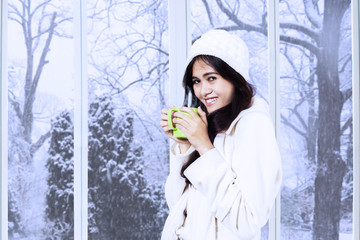 Asian lady in winter coat enjoy warm drink