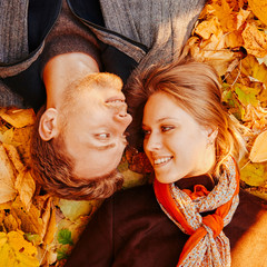 Happy loving couple lying on autumn leaves