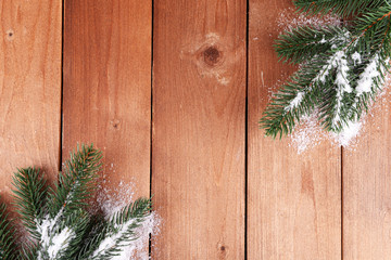 Green fir tree with snow on wooden background