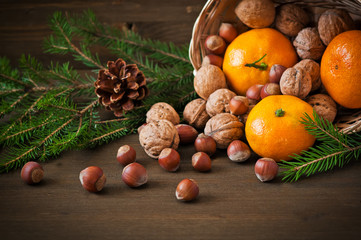 Christmas concept. Plate  with tangerine, cone and walnut
