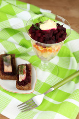 Russian herring salad in glass bowl and sandwiches with salted