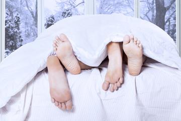 Couple feet sleeping on bed