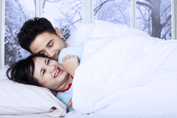 Couple joking on bed in winter day
