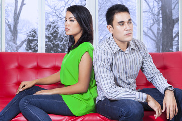 Couple sitting on sofa with mad expression