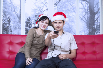 Couple wearing christmas hat watching tv