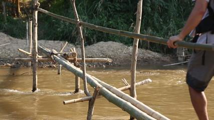 Man crossing bamboo bridge
