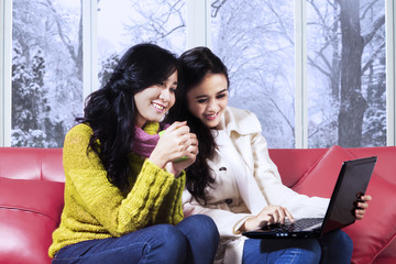 Girls in winter clothes using laptop