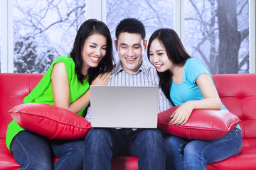 Group of friends using laptop on sofa