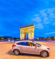 Car with mother and daughter in front of Triumph Arc at night in