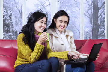 Happy girls in warm clothes using laptop