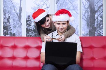 Hispanic couple pay online at home