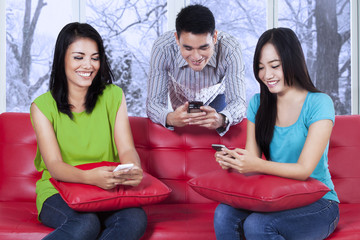 Joyful teenager texting with cellphone
