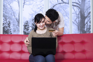 Man kissing her wife while pay online