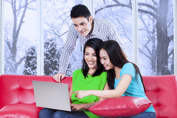 Three teenagers with laptop at home