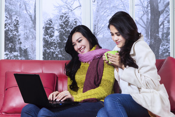 Two ladies using laptop in winter day