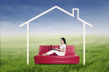 Woman using laptop with house picture