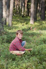 Smiling boy picking berries in a straw hat