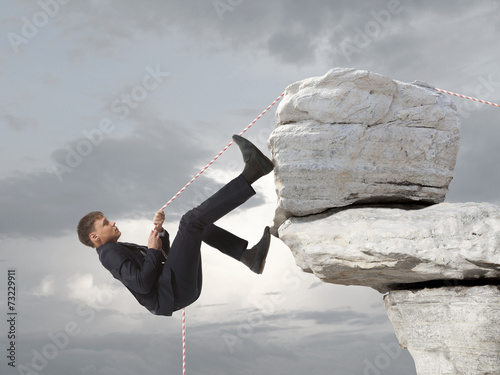 Poster Young businessman scaling a rock