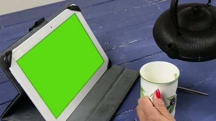 a young woman drinking tea with a green screen digital tablet