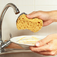 Hands with sponge and dirty dishes over the sink in the kitchen