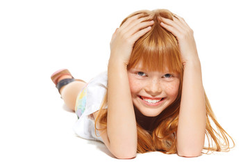 A cheerful little girl with red hair is lying; isolated