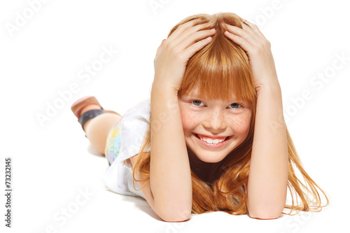 canvas print picture A cheerful little girl with red hair is lying; isolated