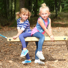 Two sisters on a garden swing.