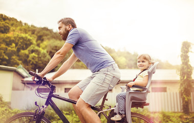 Father and daughter on bicycle in park