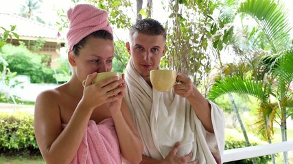 Young Couple Drinking Coffee after Shower in Towels.
