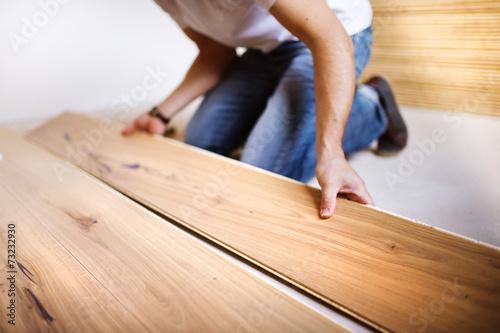Handyman installing wooden floor - 73232930