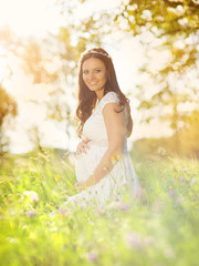 Pregnant woman in white dress in nature