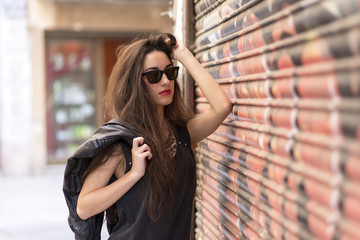 Portrait of beautiful casual woman with sunglasses, rockstyle.
