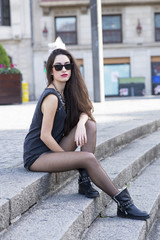 Attractive woman with sunglasses sitting on stairs, urban lifest
