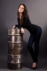 girl in jeans standing near an iron barrel