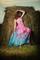Young woman standing in evening field over haystack. Fashion sty