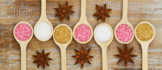 White, brown and pink sugar on wooden spoons