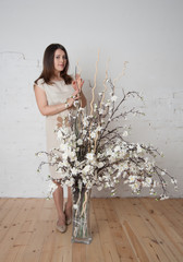 charming girl with dried flowers have a white wall