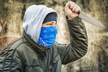 Man with knife near old wall