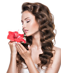 Portrait of young beautiful woman smelling flower near the face