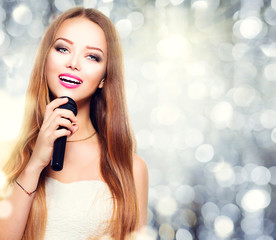Beauty model girl with a microphone singing and dancing