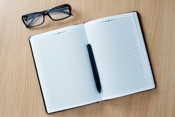 Open diary with a pen and glasses