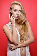 Beautiful seminude blonde woman at red background.