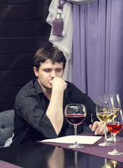 young man tasting wine at a table in a restaurant