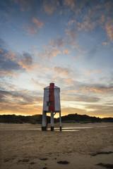 Beautiful landscape sunrise stilt lighthouse on beach